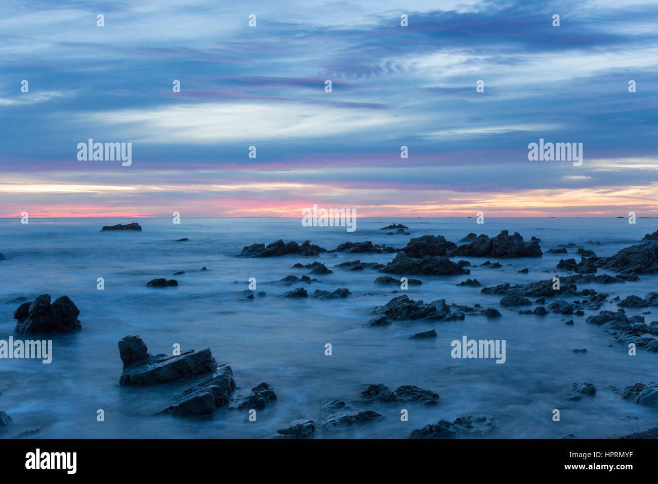 Kaikoura, Canterbury, New Zealand. View across the Pacific Ocean from rocky shoreline at dawn. - Stock Image
