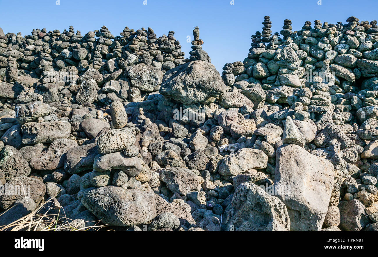 Republic of Korea, Jeju Island, East Coast, Onpyeong-ri, elaborate rock pile cairns at the coastal foreshore - Stock Image
