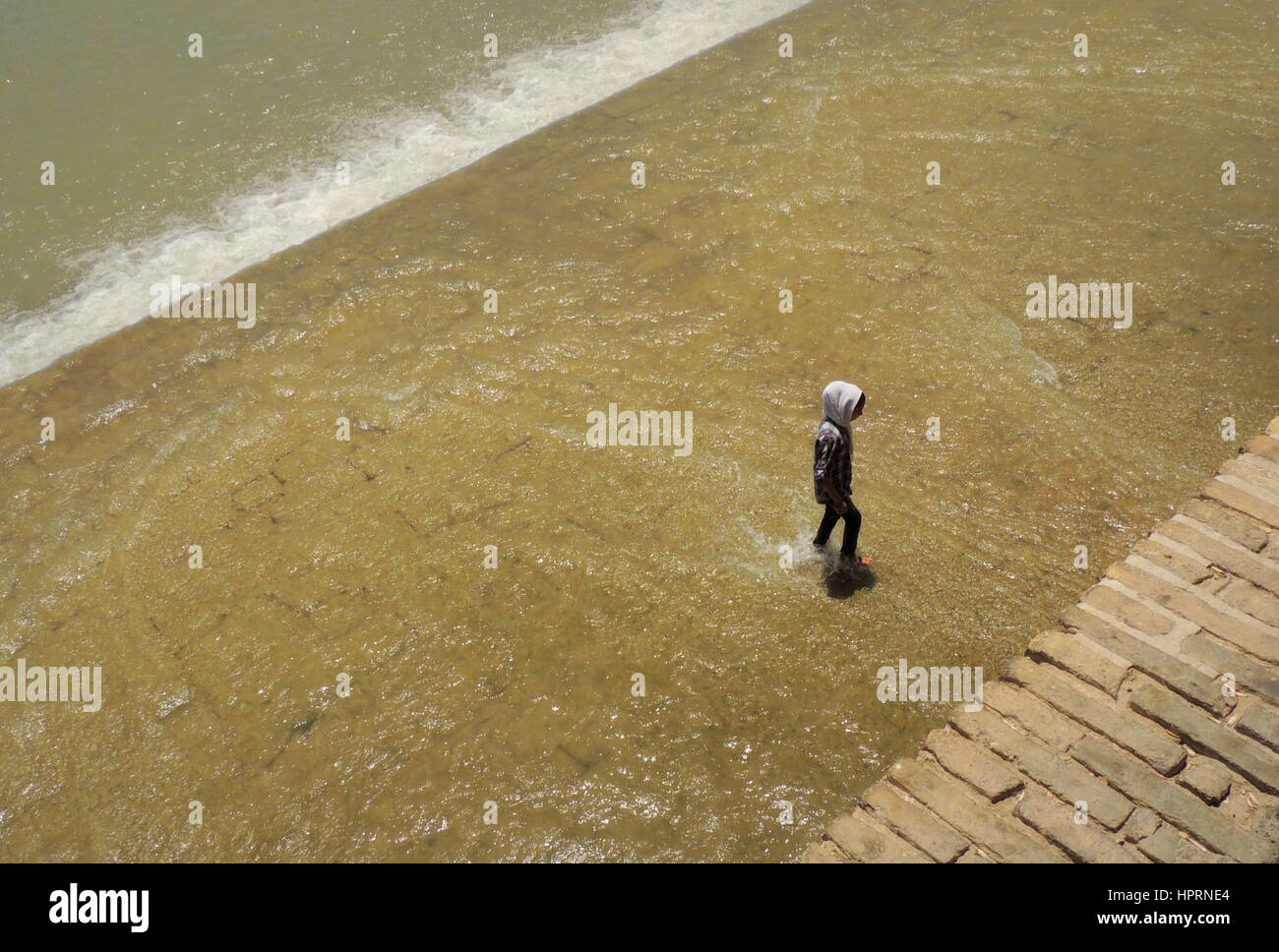 Muslim girl goes against the flow and walks alone challenging the waters of the Zayandeh river by the Si o seh pol - Stock Image