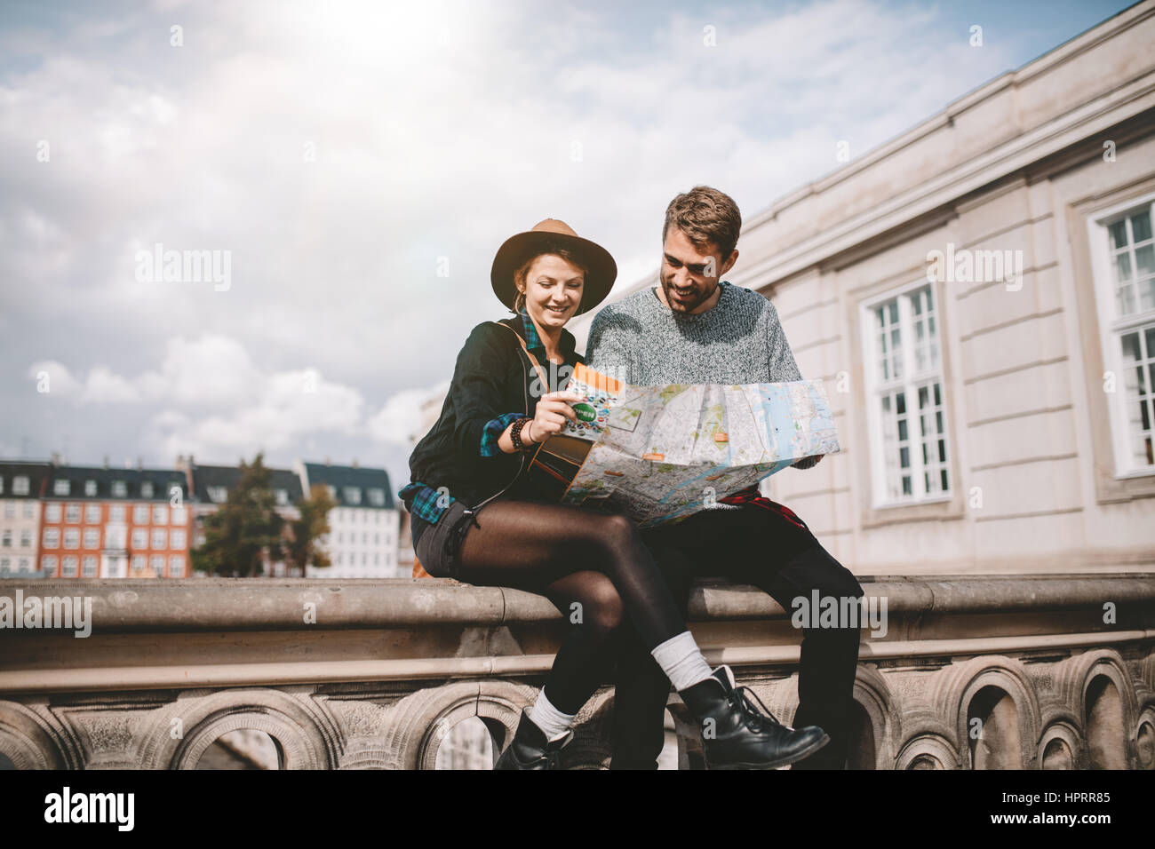 Young tourist couple exploring the navigation map of a city. Happy couple sitting on bridge on a cloudy day looking - Stock Image