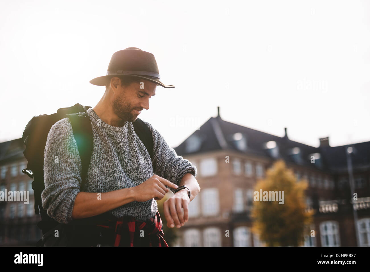 Young man wearing tourist bag and hat looking at his smart watch. Tourist smiling looking at his watch with sunlight - Stock Image