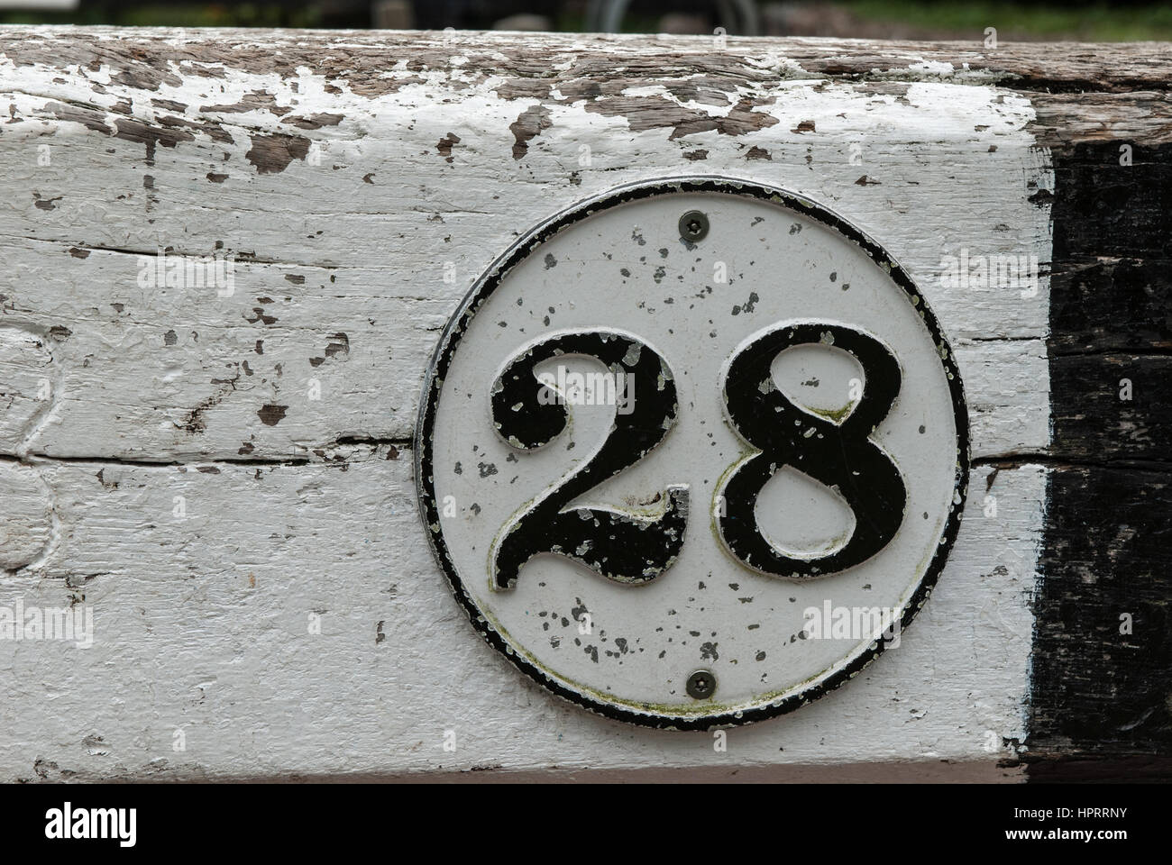 The number 28 black on white in a circular border painted against a white and black wooden background. - Stock Image