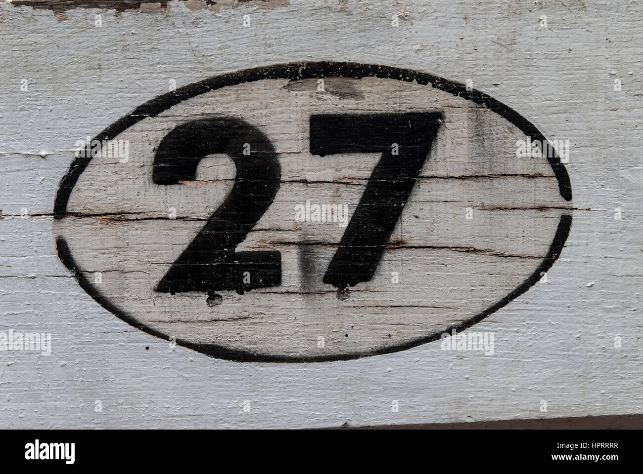 The number 27 black on white in an oval border painted against a white wooden background. - Stock Image