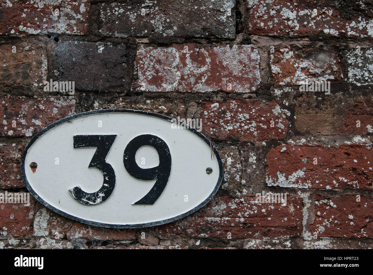 An oval plaque depicting the number 39 against a brick background. - Stock Image