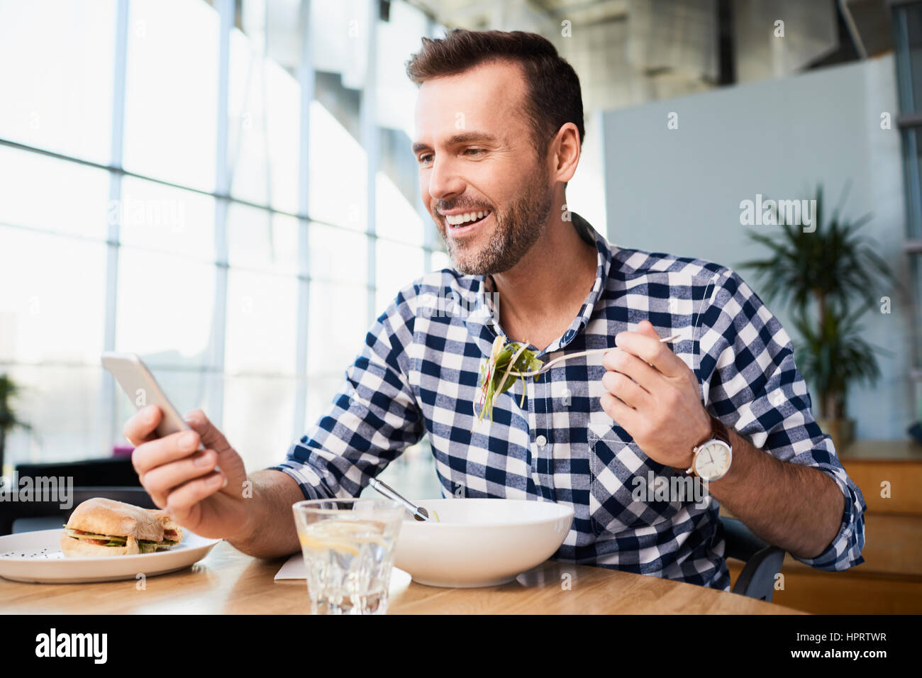 Handsome man in cafe holding fork in one hand and smartphone in another, looking at smartphone and smiling Stock Photo