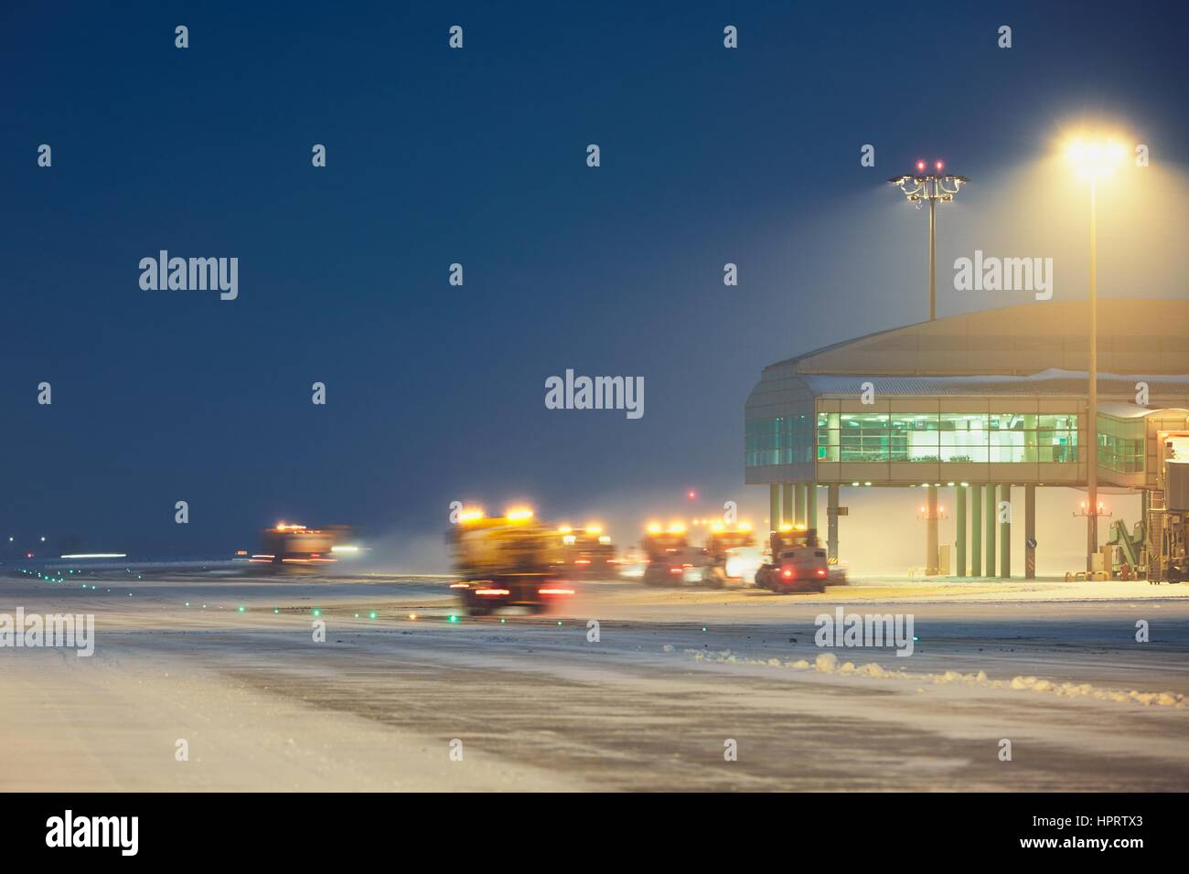 Airport during the snowstorm. Snow plows cleared the snow from the runways and taxiways. - selective focus on terminal - Stock Image