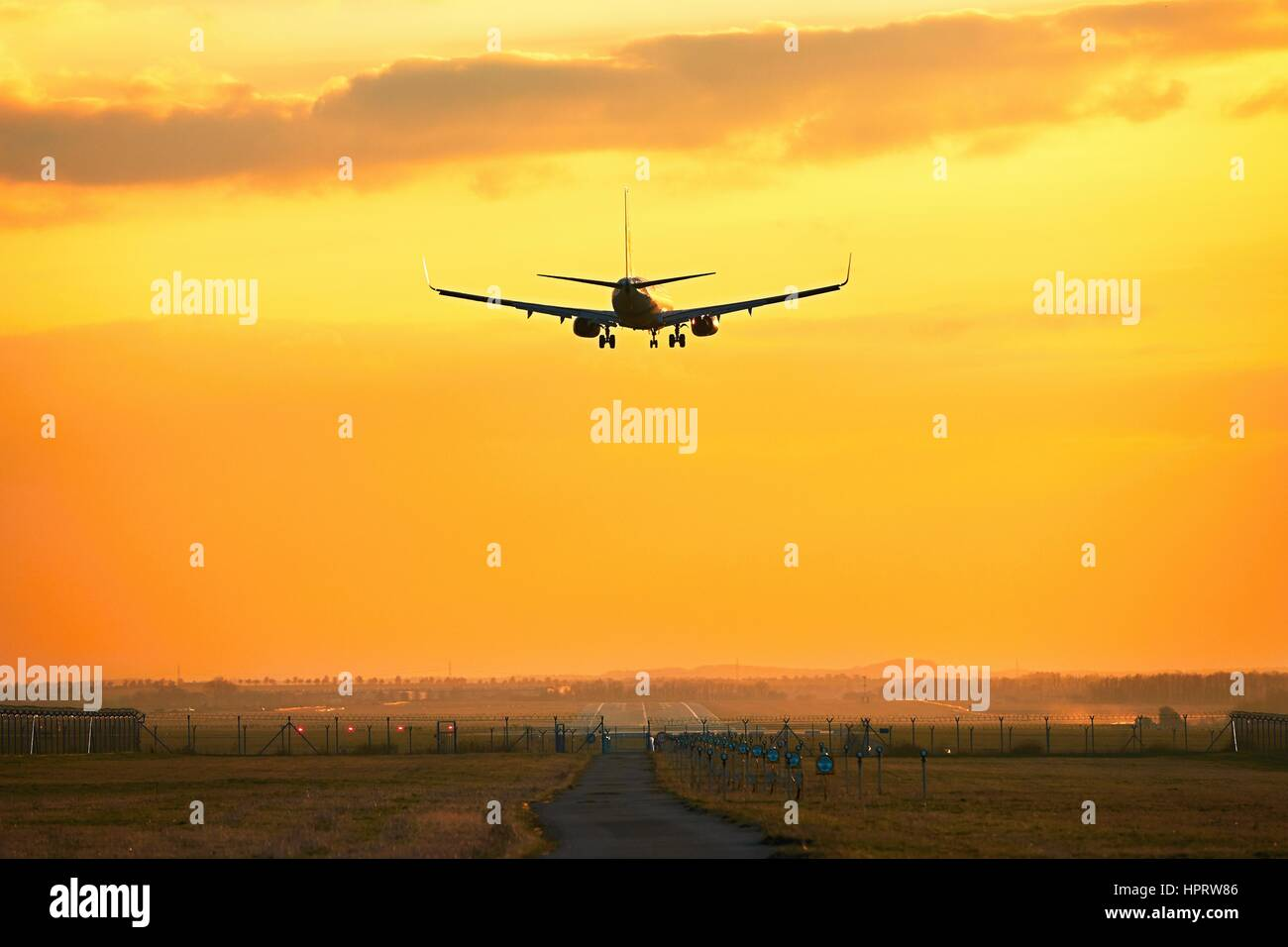 Silhouette of the airplane during landing at the airport - Stock Image