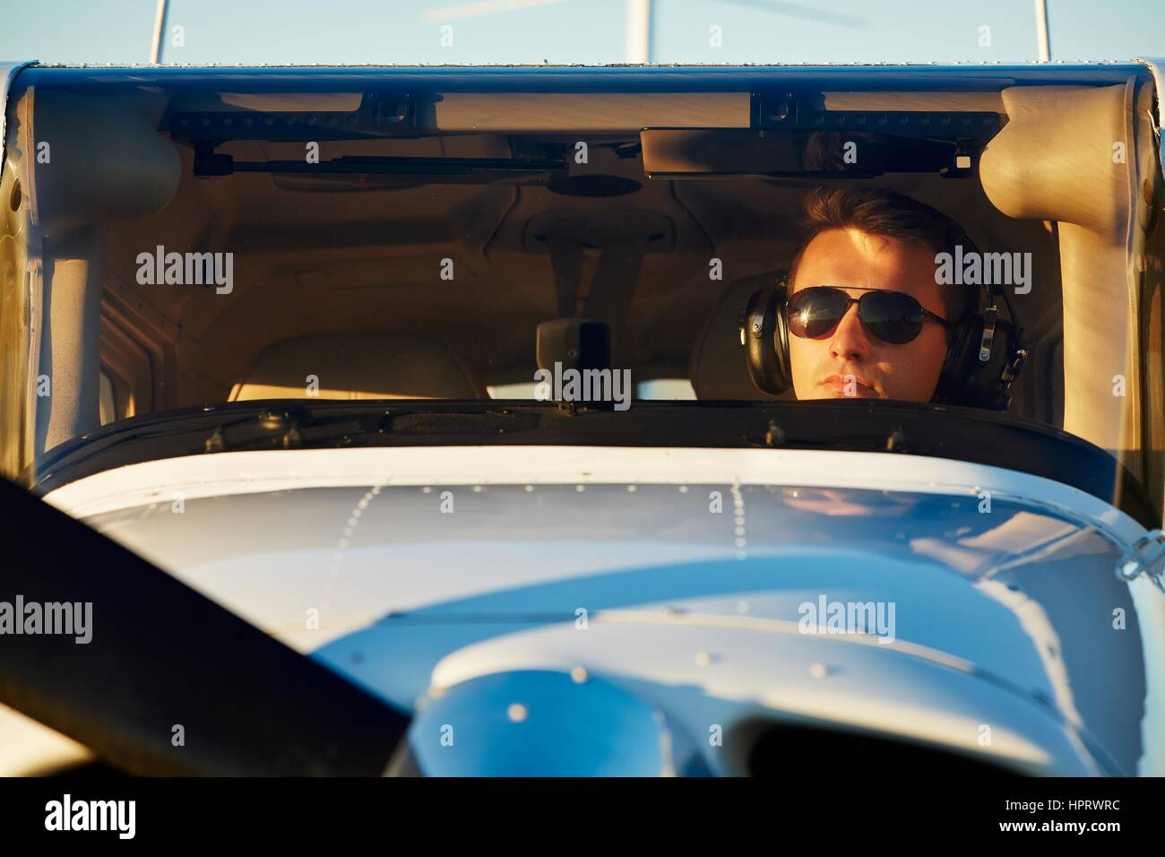 Young pilot is preparing for take off with private plane. - Stock Image