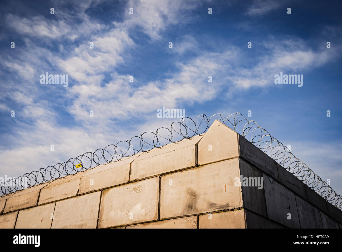 A wall topped with protective coils of razor wire - Stock Image