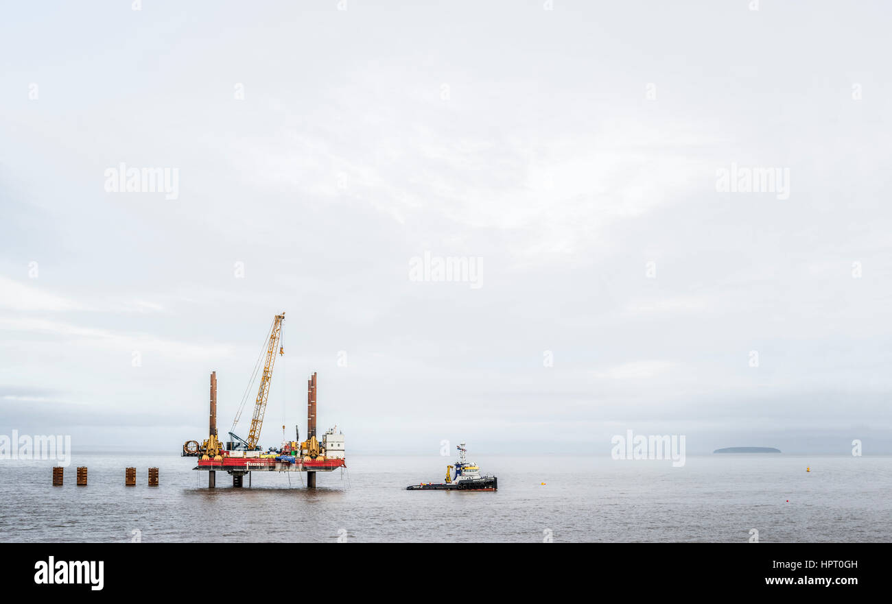 Offshore rig and boat in the Bristol channel,druring the construction of Hinhley C power station. - Stock Image