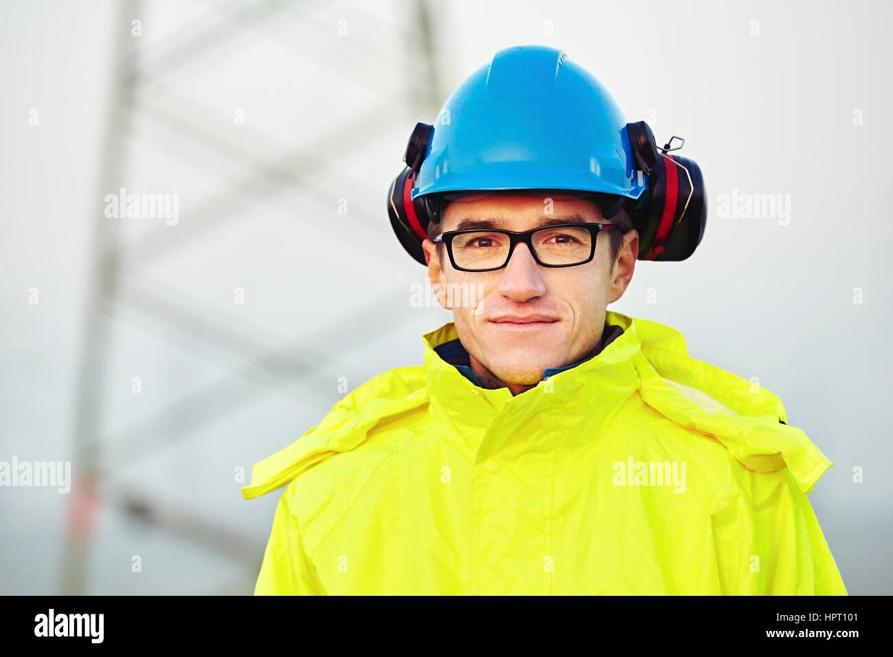 Worker wearing reflective clothing with helmet. - Stock Image