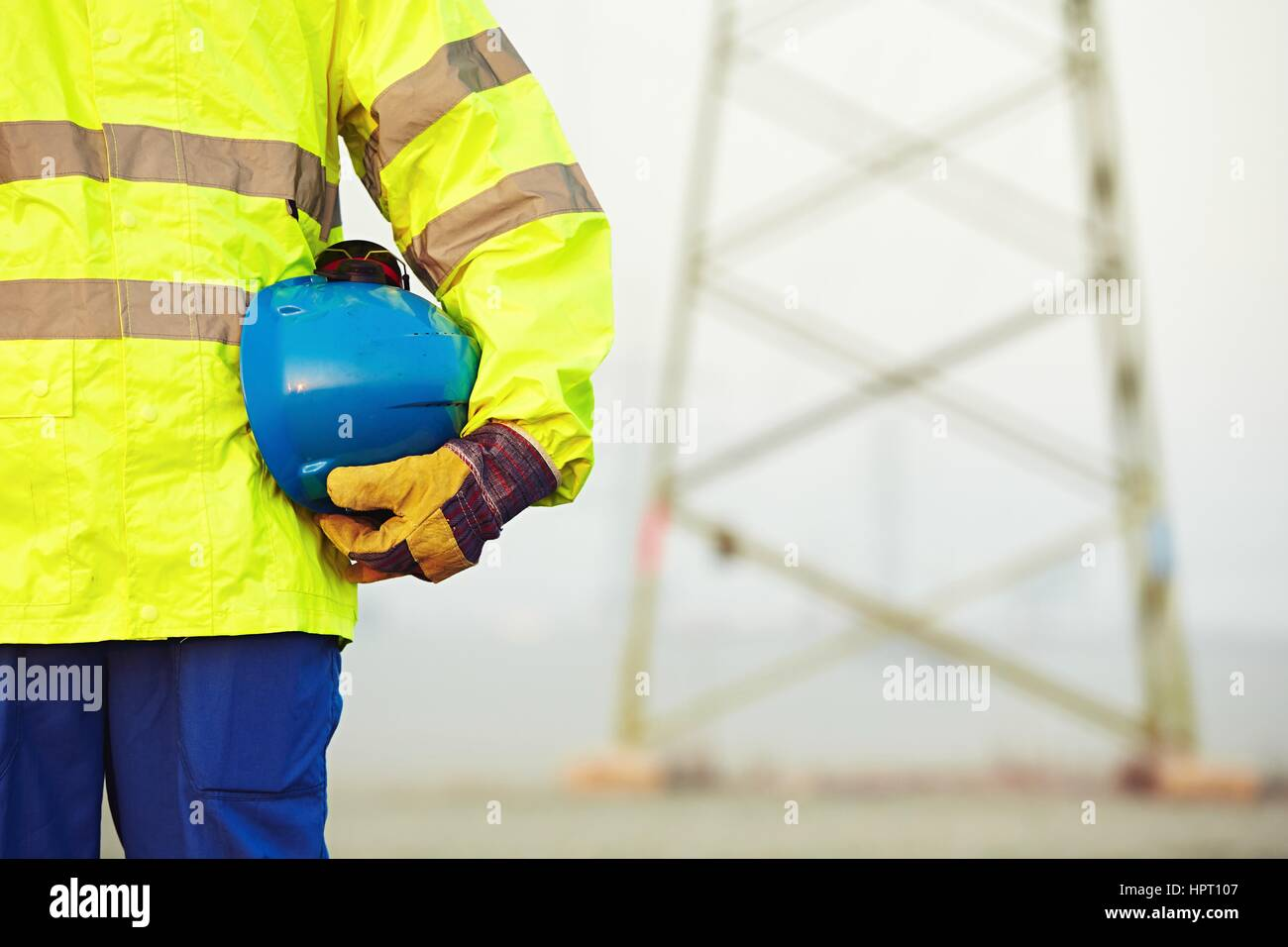 Arm of worker is holding protective helmet - Stock Image
