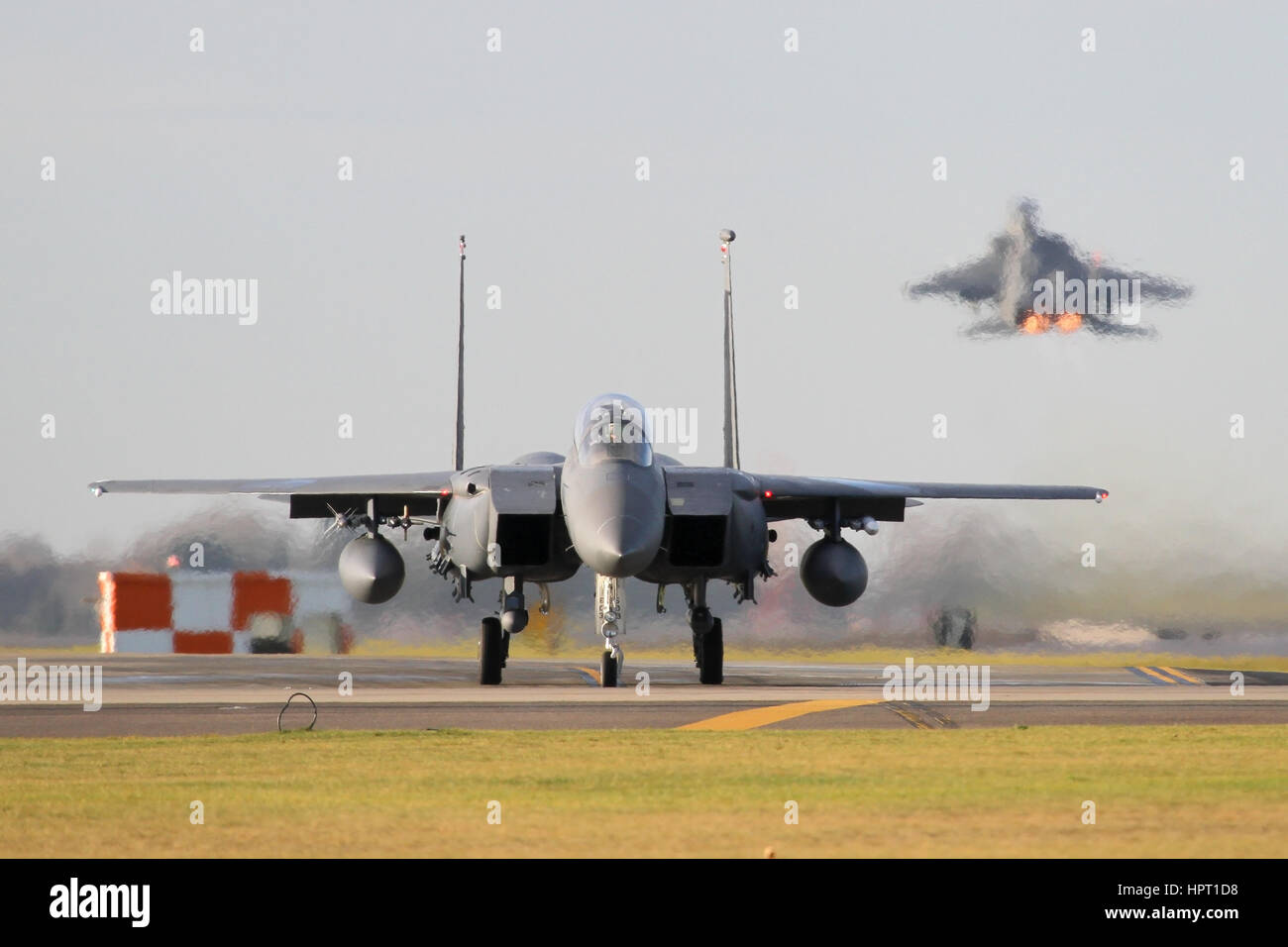 One F-15E  from the 48th Fighter Wing rotates off the runway at RAF Lakenheath as another taxies to the runway. - Stock Image