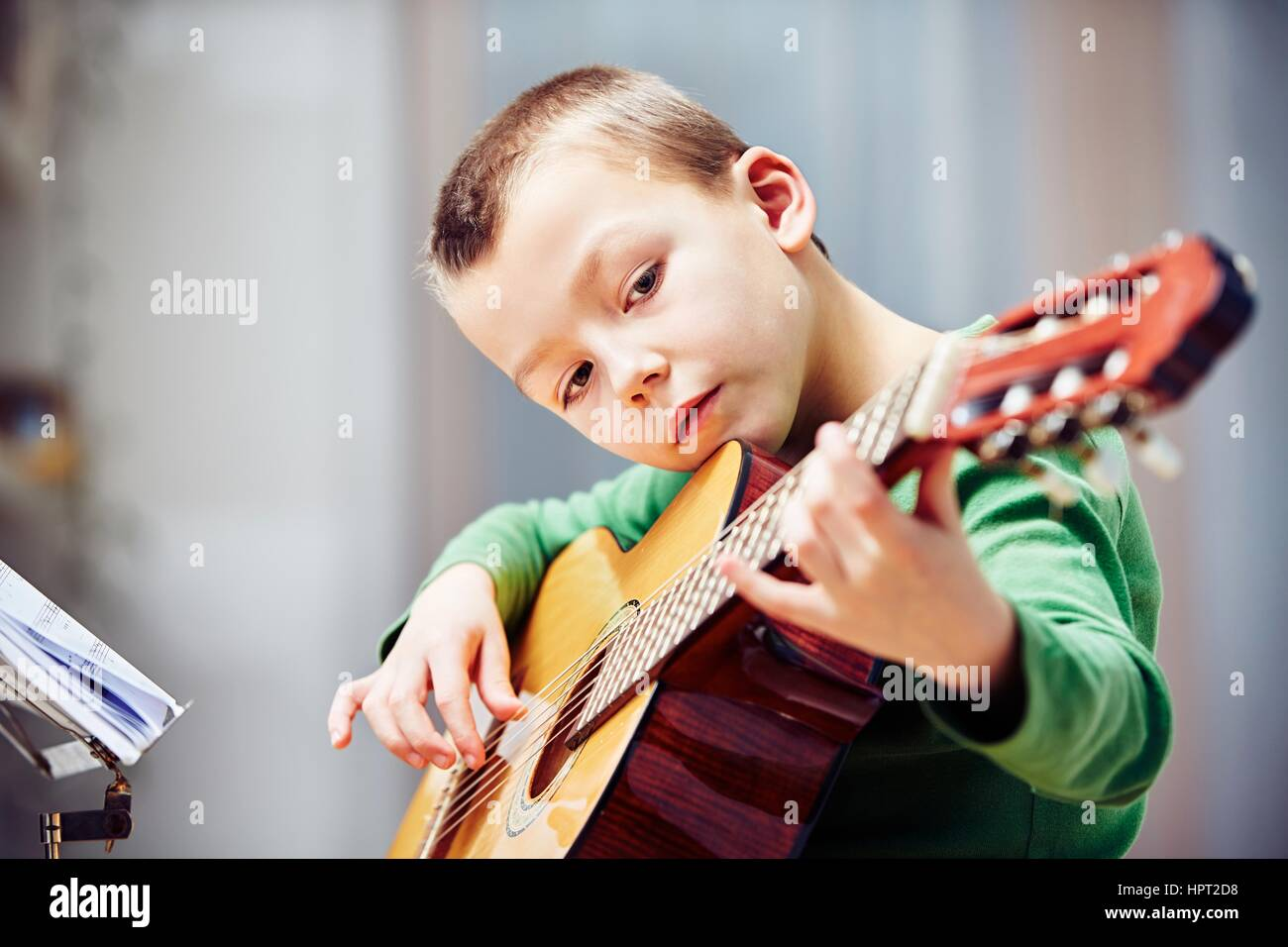 Little boy is playing the guitar at home - Stock Image