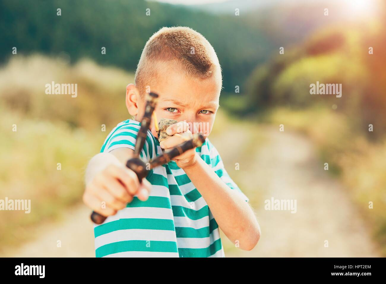 Naughty boy holding slingshot with stone. Little boy is playing in rural landscape. Stock Photo