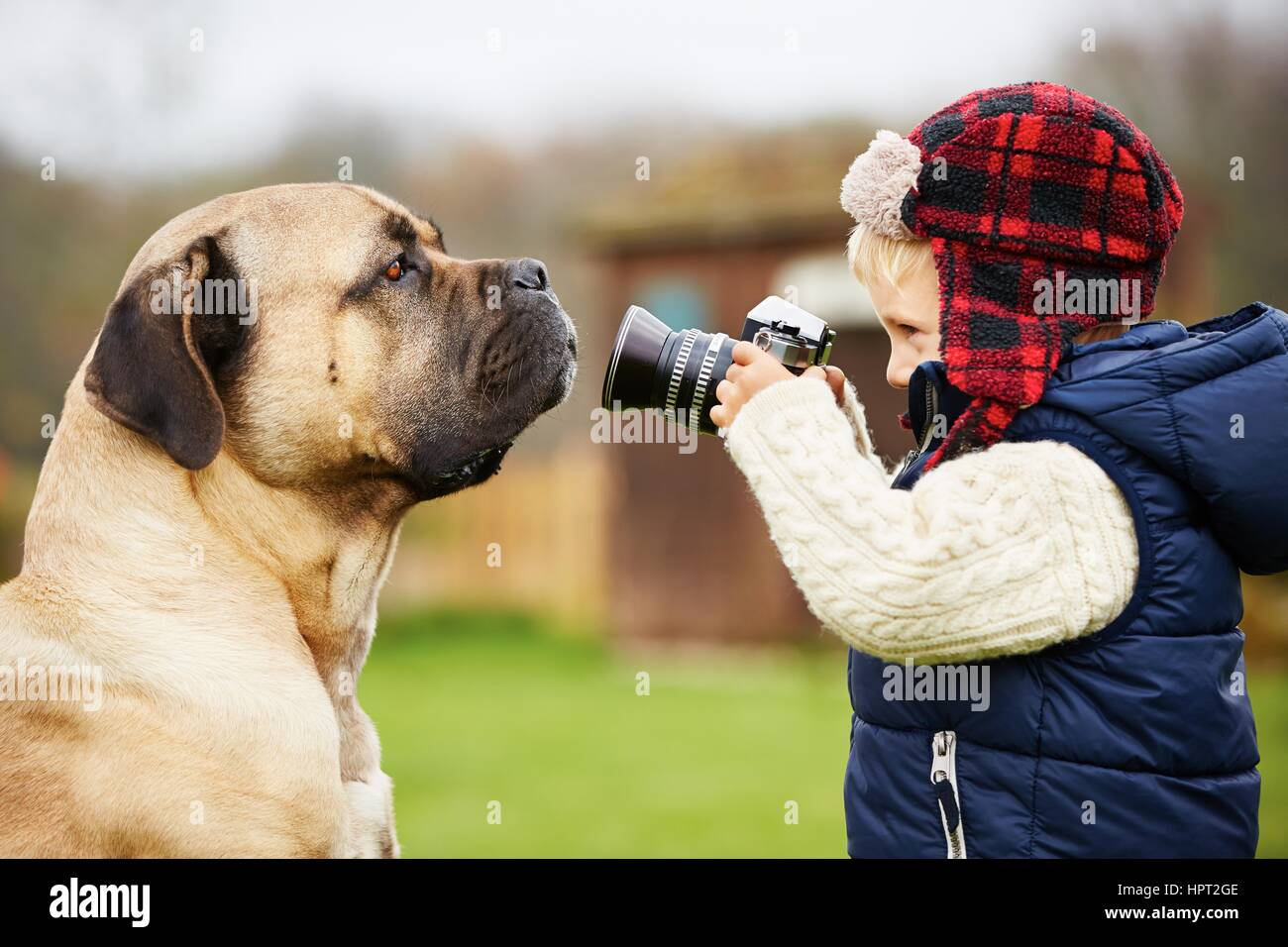 Little boy with camera is shooting his dog - Stock Image