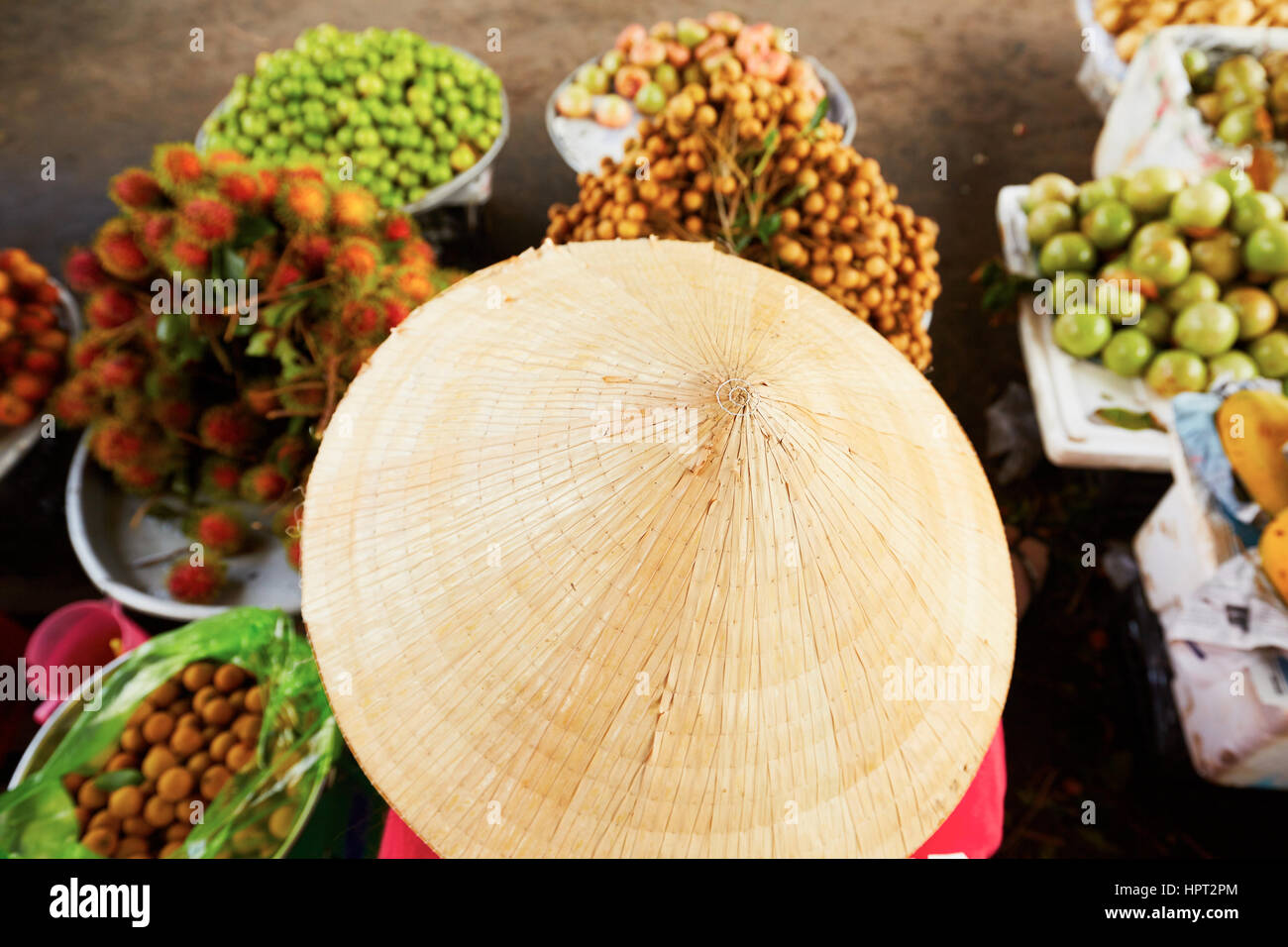 Vietnamese woman selling fruits on the street market - selective focus - Stock Image