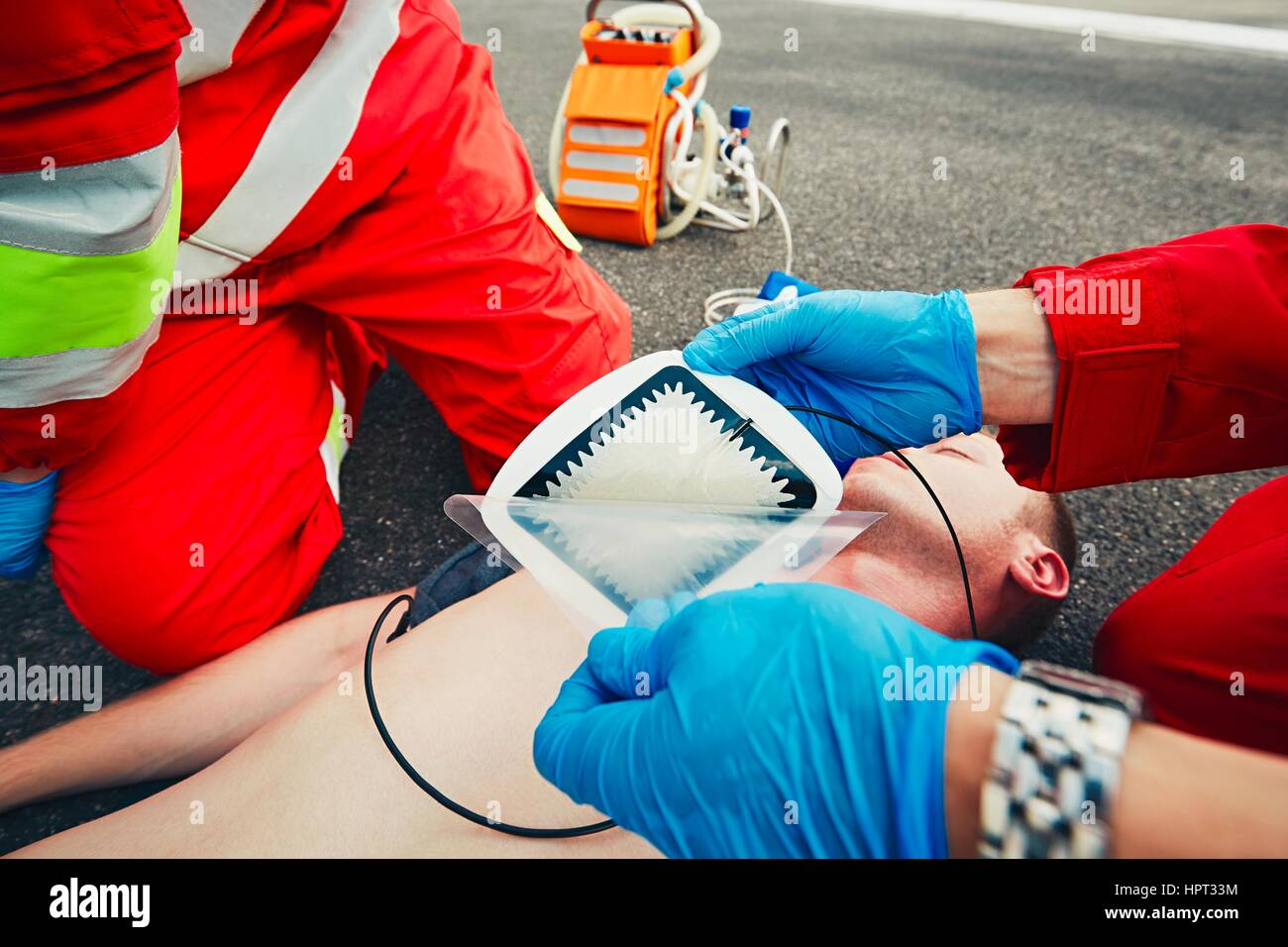 Electrodes of the defibrillator. Rescue team (doctor and a paramedic) resuscitating the man on the street. - Stock Image