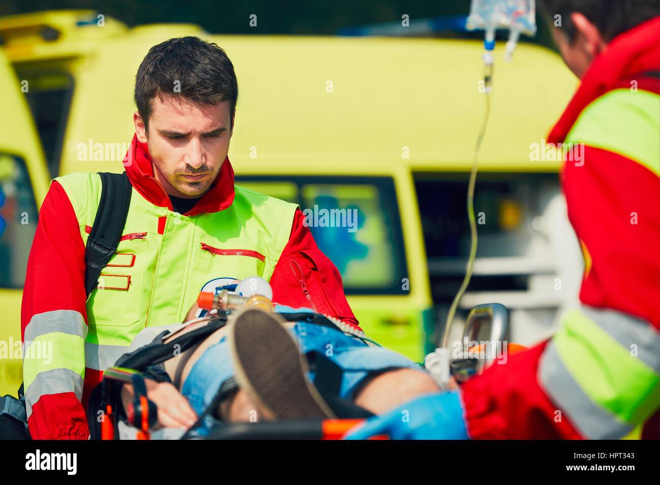 Team of rescuers (paramedic and doctor) preparing the patient after resuscitation for transport to the hospital. - Stock Image