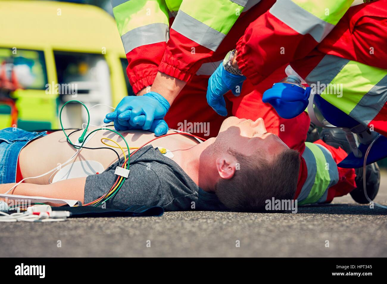 Cardiopulmonary resuscitation. Rescue team (doctor and a paramedic) resuscitating the man on the street. - Stock Image