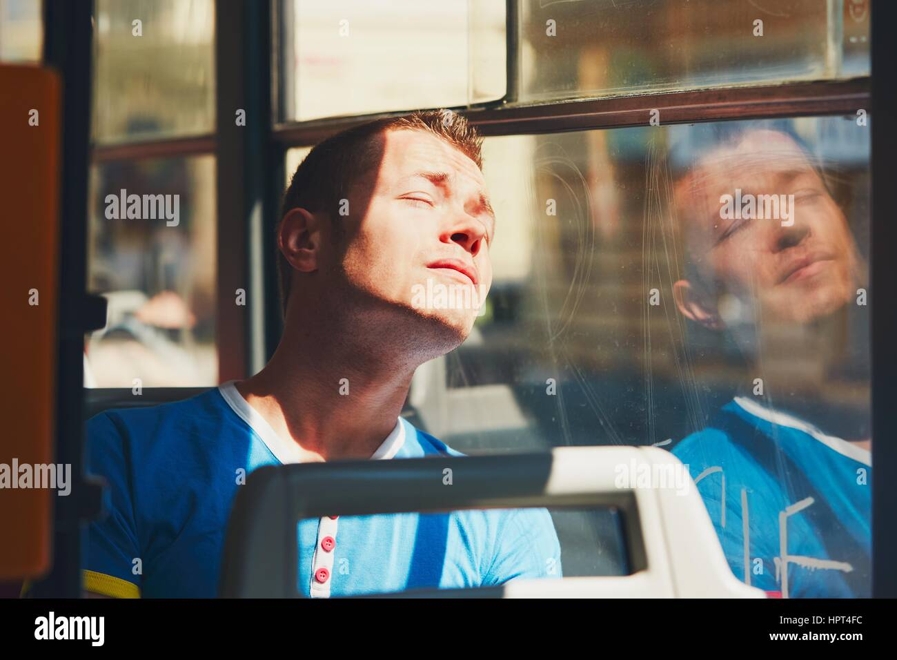 Everyday life and commuting to work by public transportation. Handsome young man is traveling by tram (bus). Tired - Stock Image