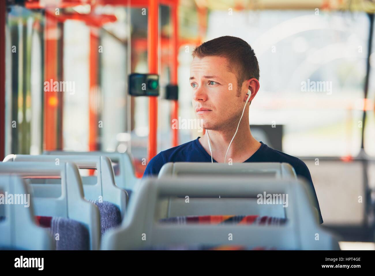 Sad young man is traveling by tram (bus). Everyday life and commuting to work by public transportation. Man is wearing Stock Photo