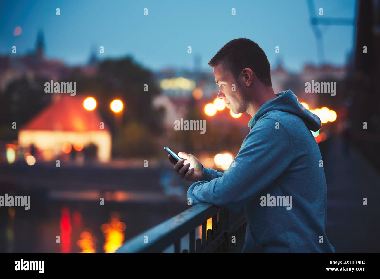 Alone in the night city with mobile phone. Handsome dreamy man reading message (or looking on the video) on his - Stock Image