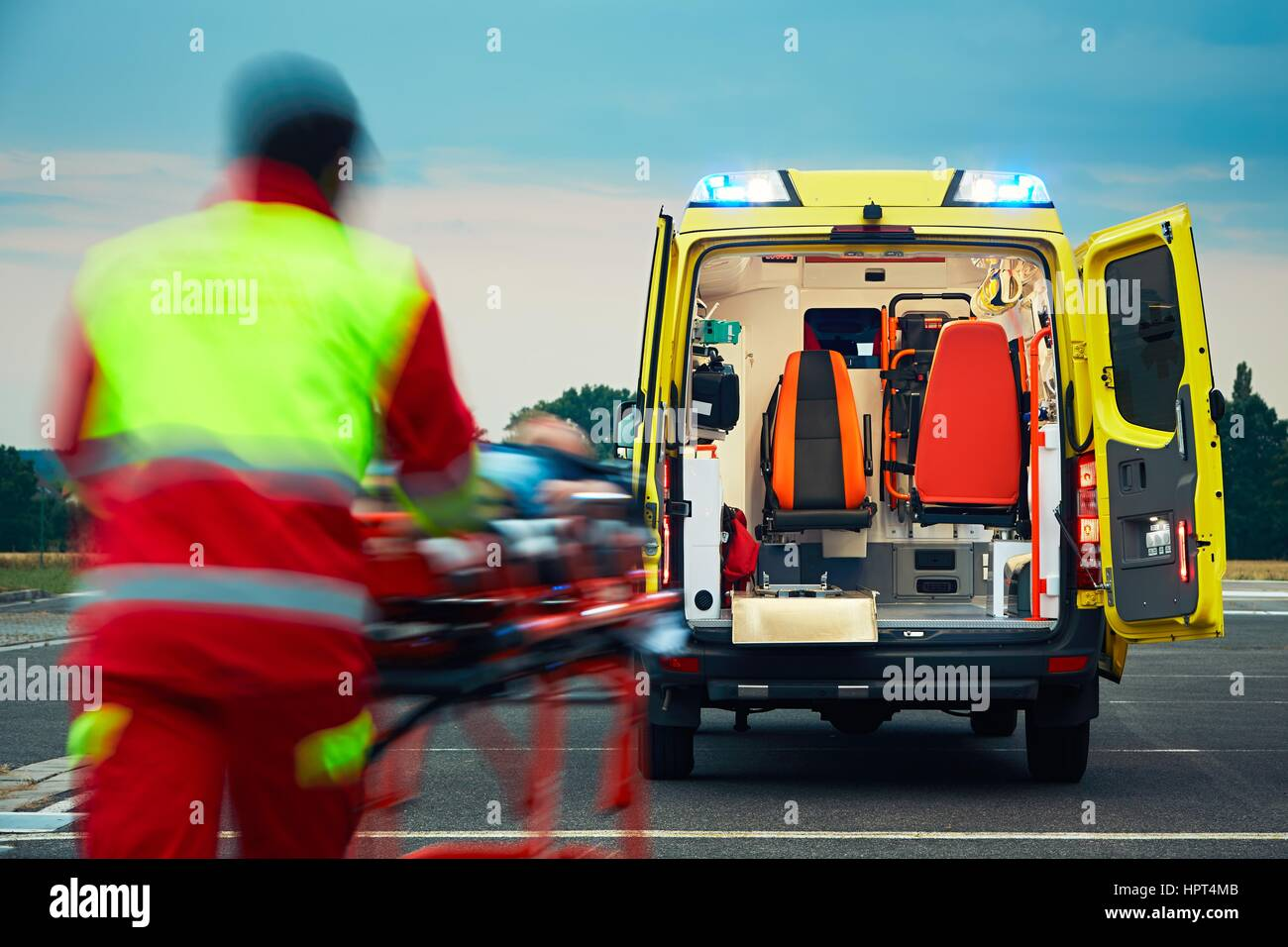Emergency medical service. Paramedic is pulling stretcher with patient to the ambulance car. - Stock Image