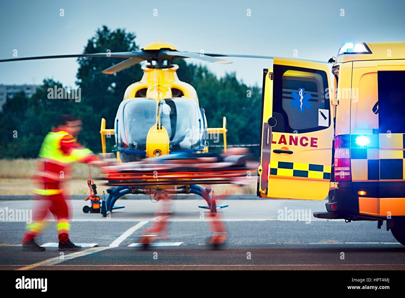 Cooperation between air rescue service and emergency medical service on the ground. Paramedic is pulling stretcher - Stock Image