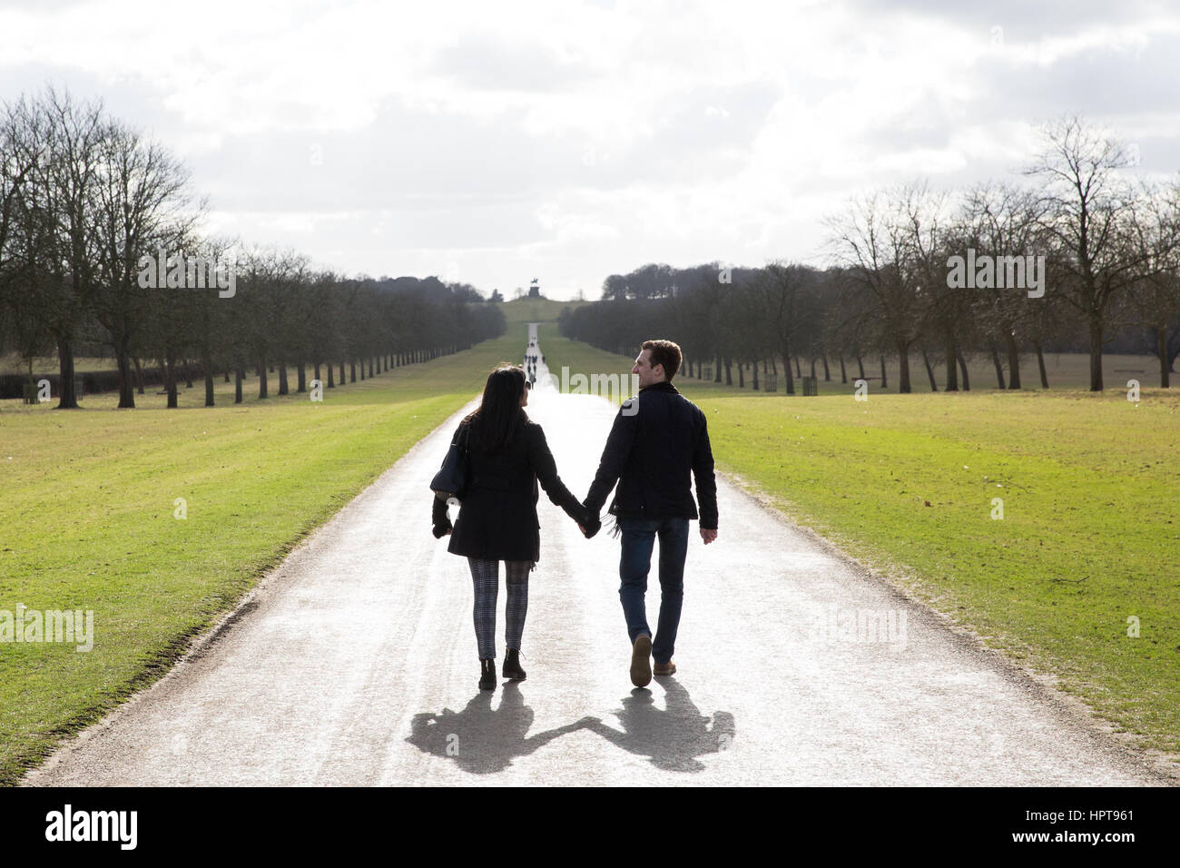 Windsor, UK. 24th February, 2017. A man and a woman walk hand in hand in fine weather on the Long Walk in WindsorStock Photo