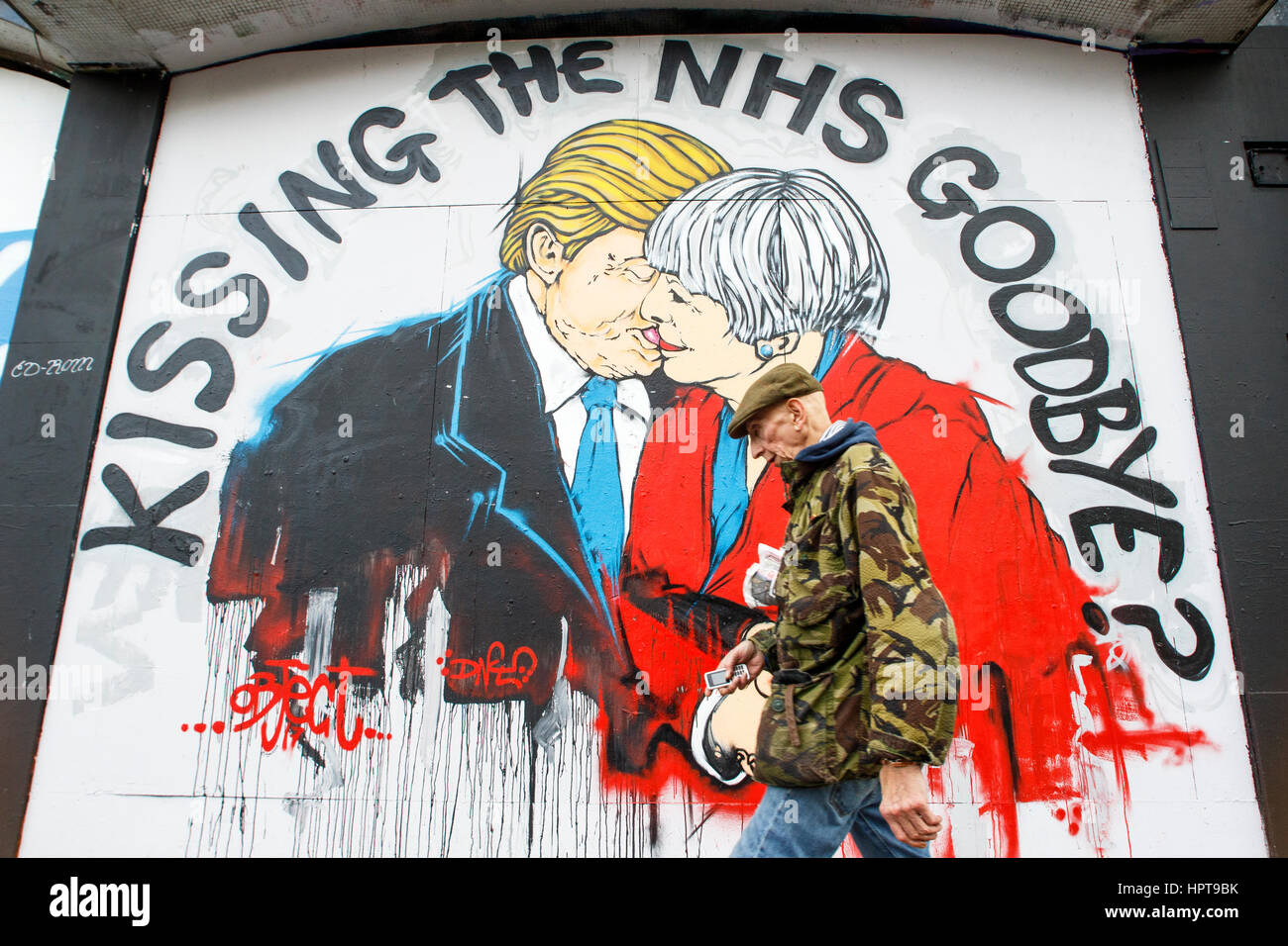 Bristol, UK. 24th Feb, 2017. A man is pictured walking past a new piece of street art warning about the death of - Stock Image