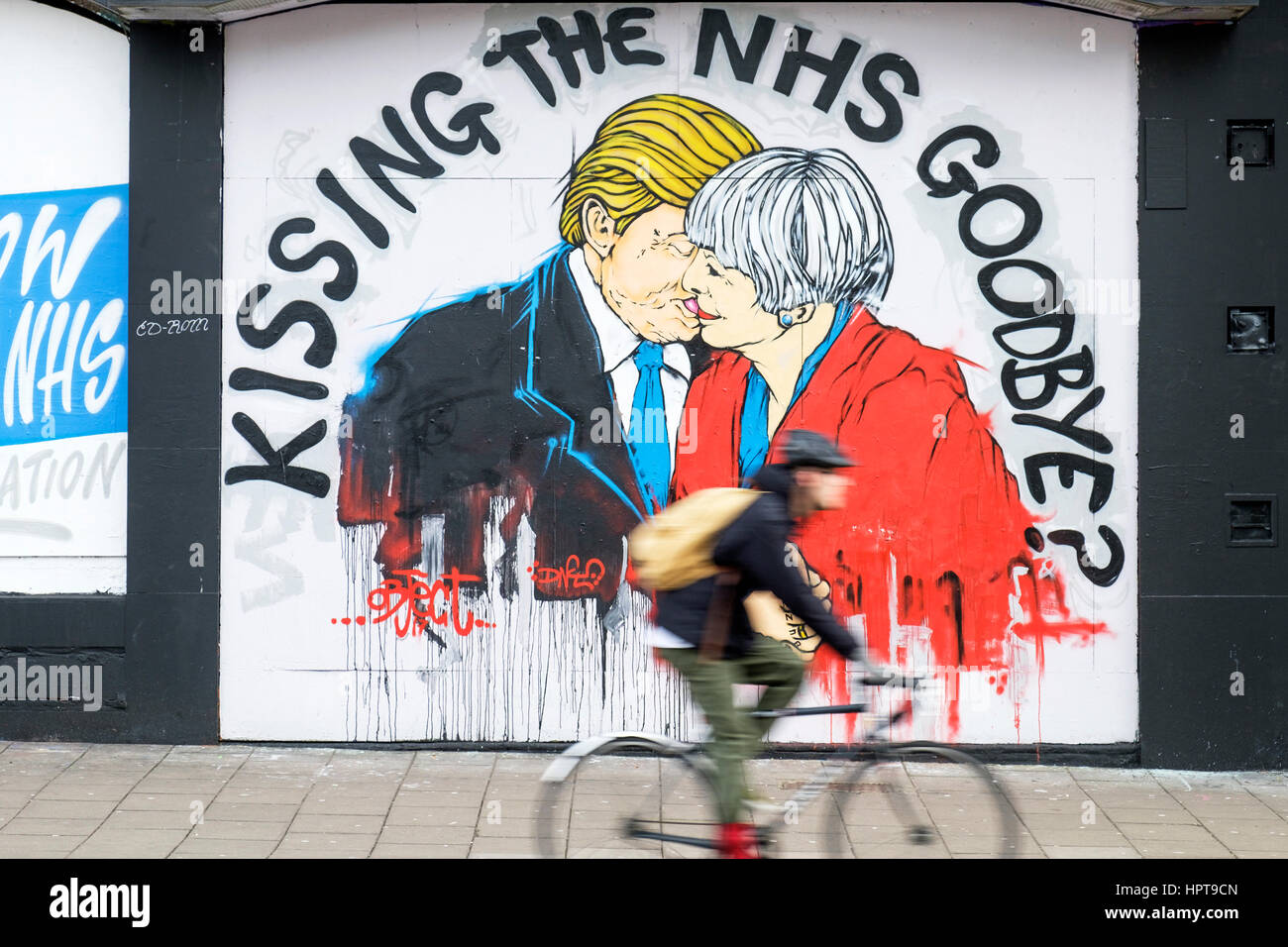 Bristol, UK. 24th Feb, 2017. A man is pictured cycling past a new piece of street art warning about the death of - Stock Image
