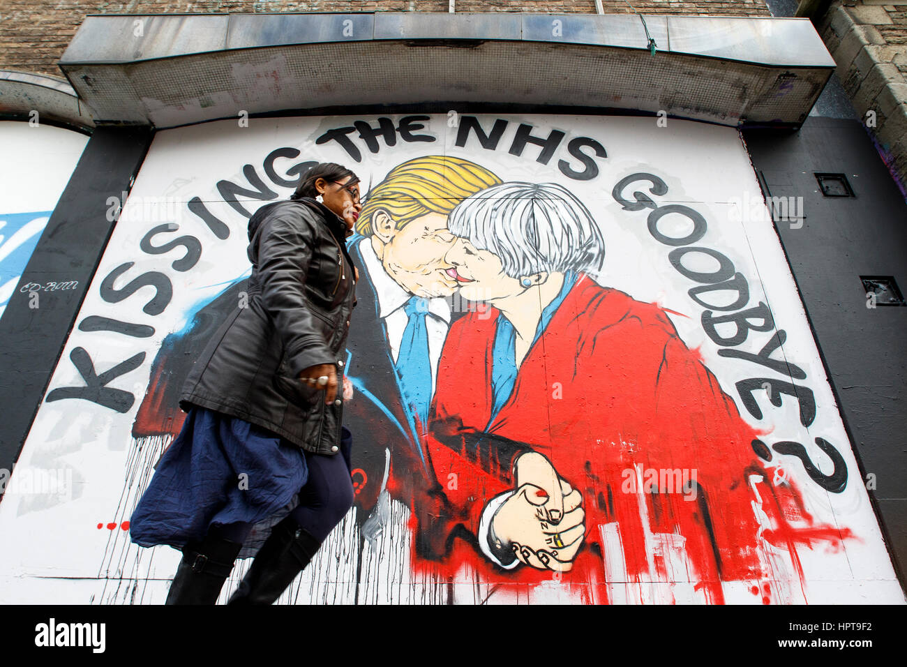 Bristol, UK. 24th Feb, 2017. A woman is pictured walking past a new piece of street art warning about the death - Stock Image