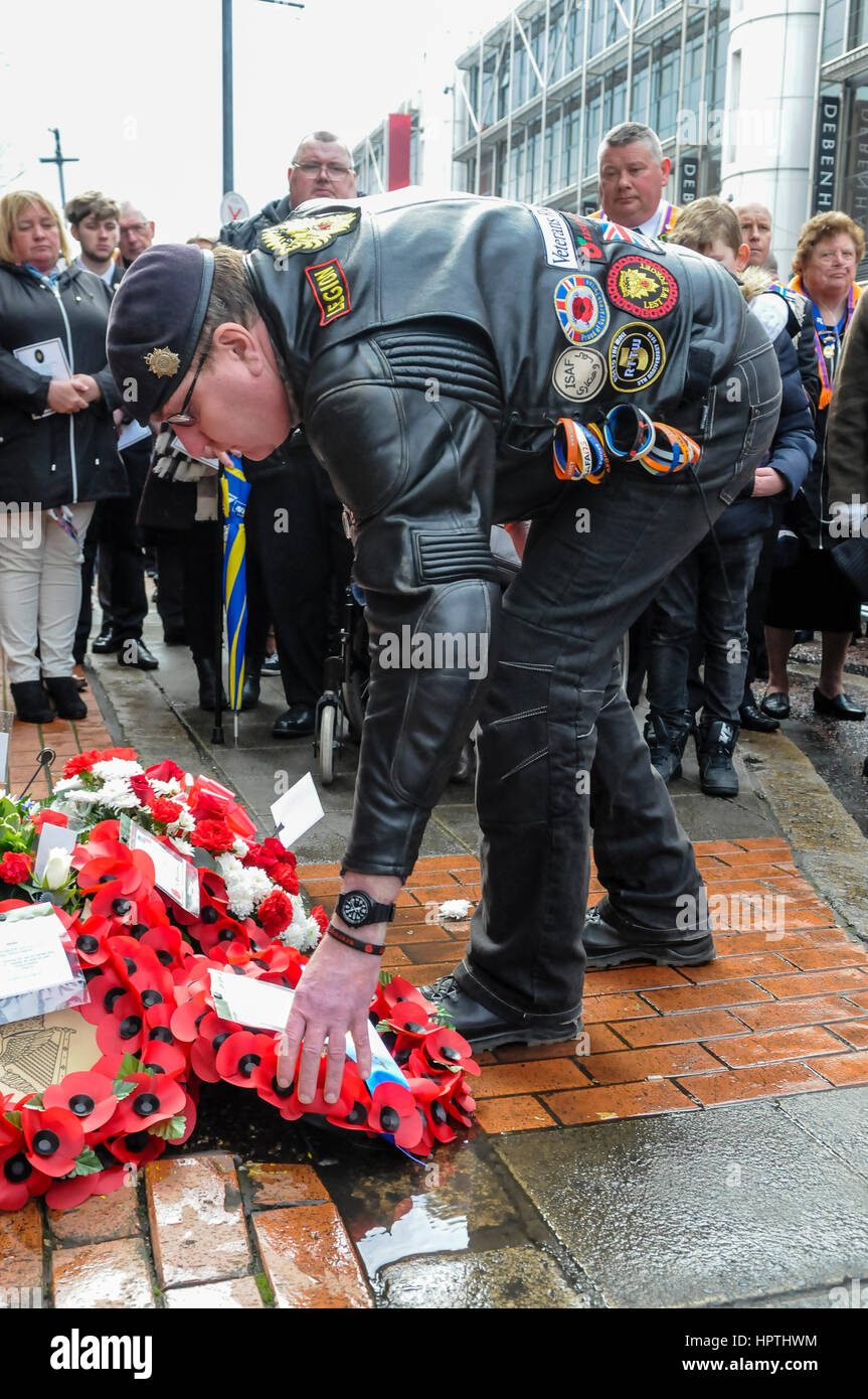 Belfast, Northern Ireland. 25 Feb 2017 - Ex soldier wearing leather motorcycle jacket with patches and badges, lays - Stock Image