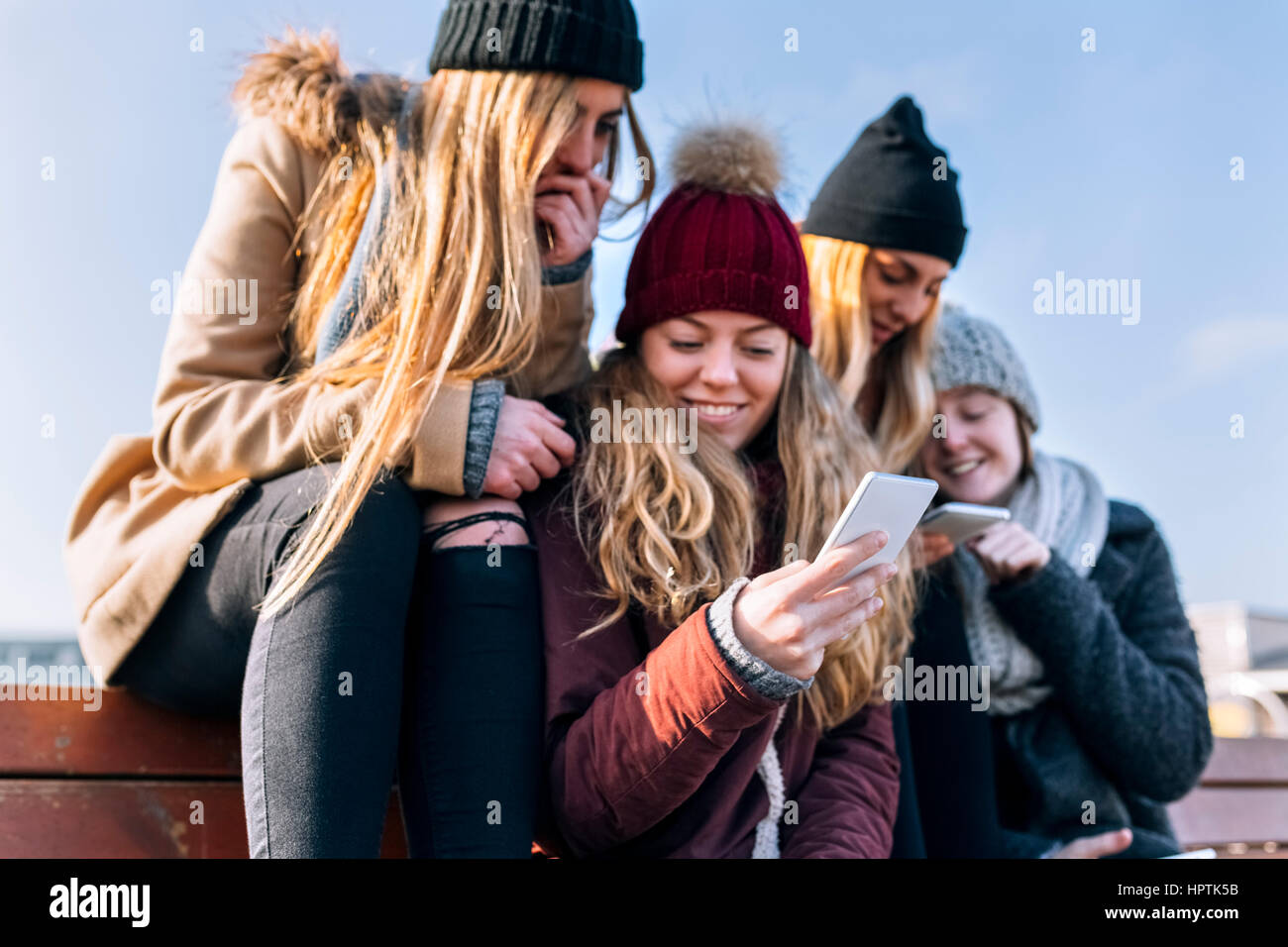 Four friends looking at cell phones - Stock Image