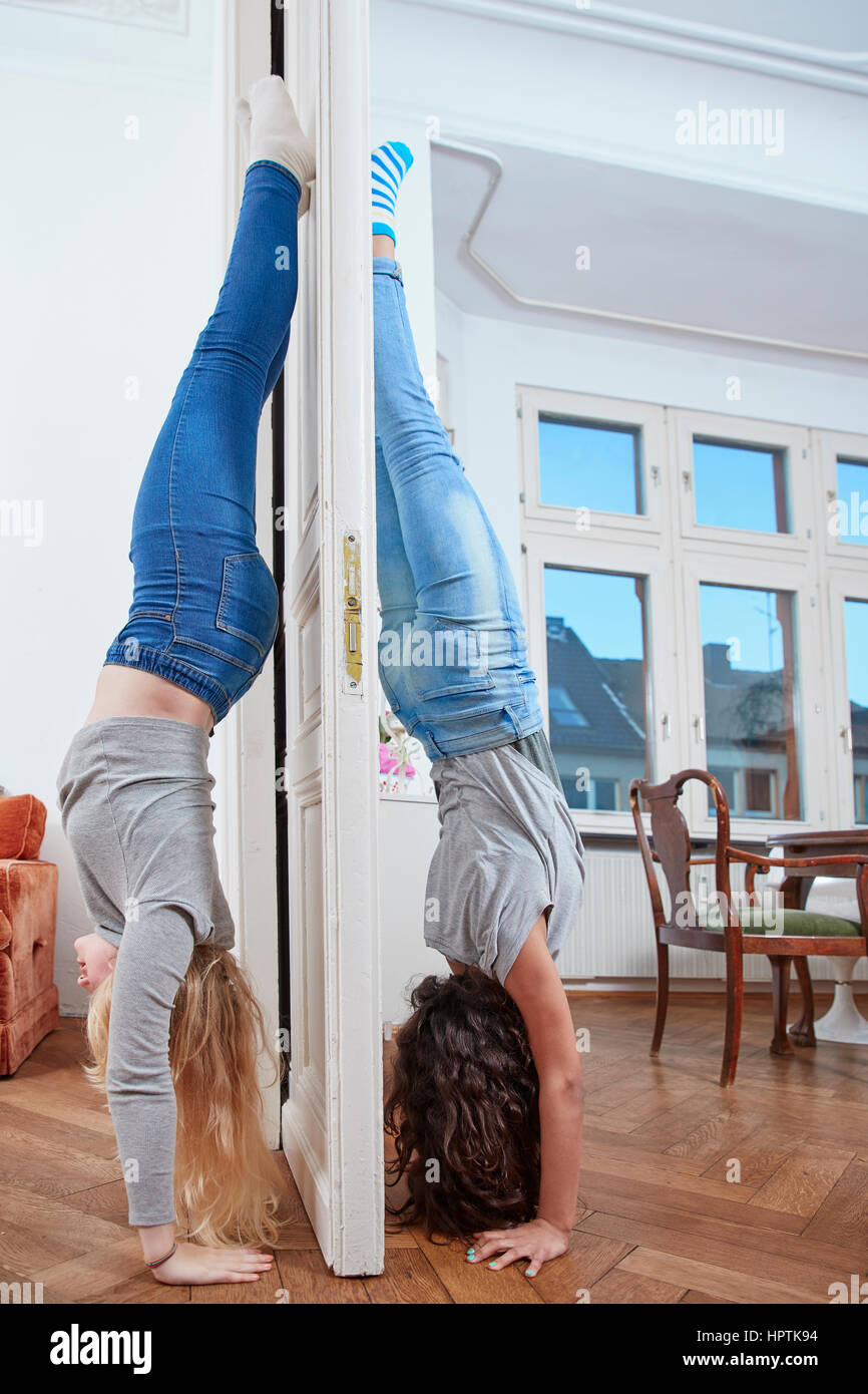 Two Girls Doing A Handstand On Opposite Sides Of A Door