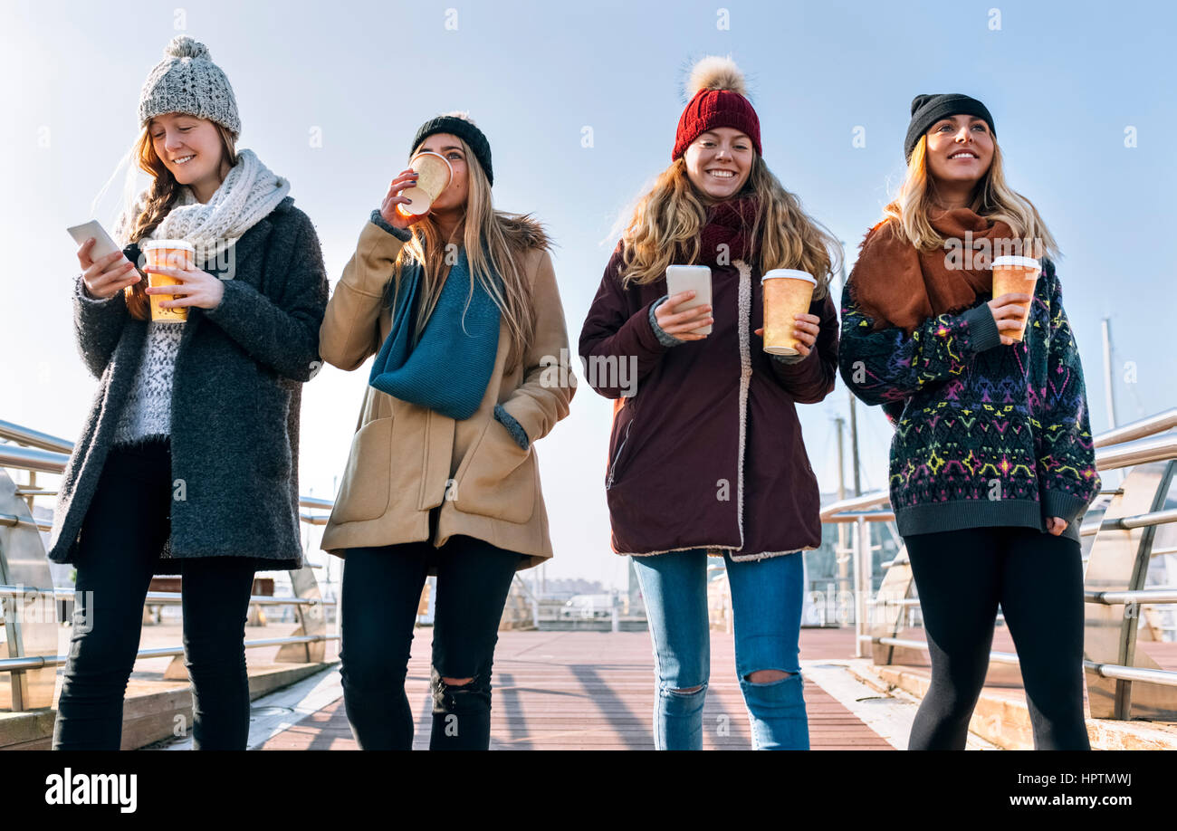 Four friends with coffee to go and cell phones walking on a bridge in winter - Stock Image