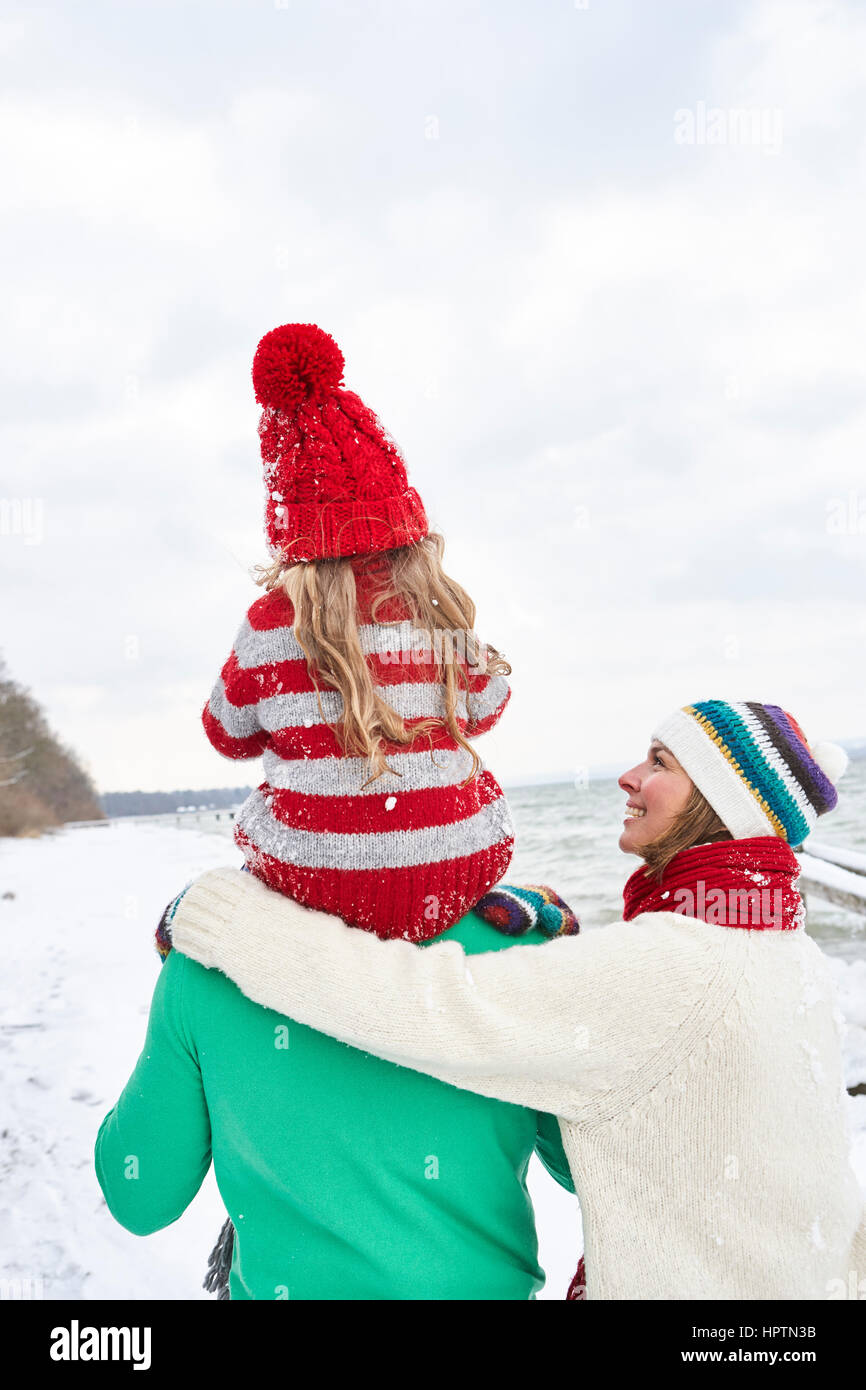 Family walking in the snow, rear view - Stock Image