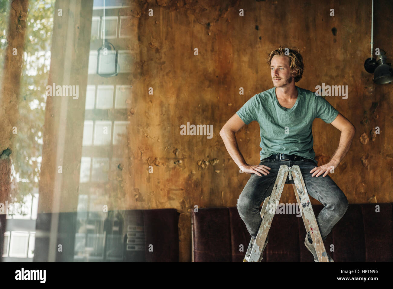 Man sitting on stepladder in unfinished room Stock Photo