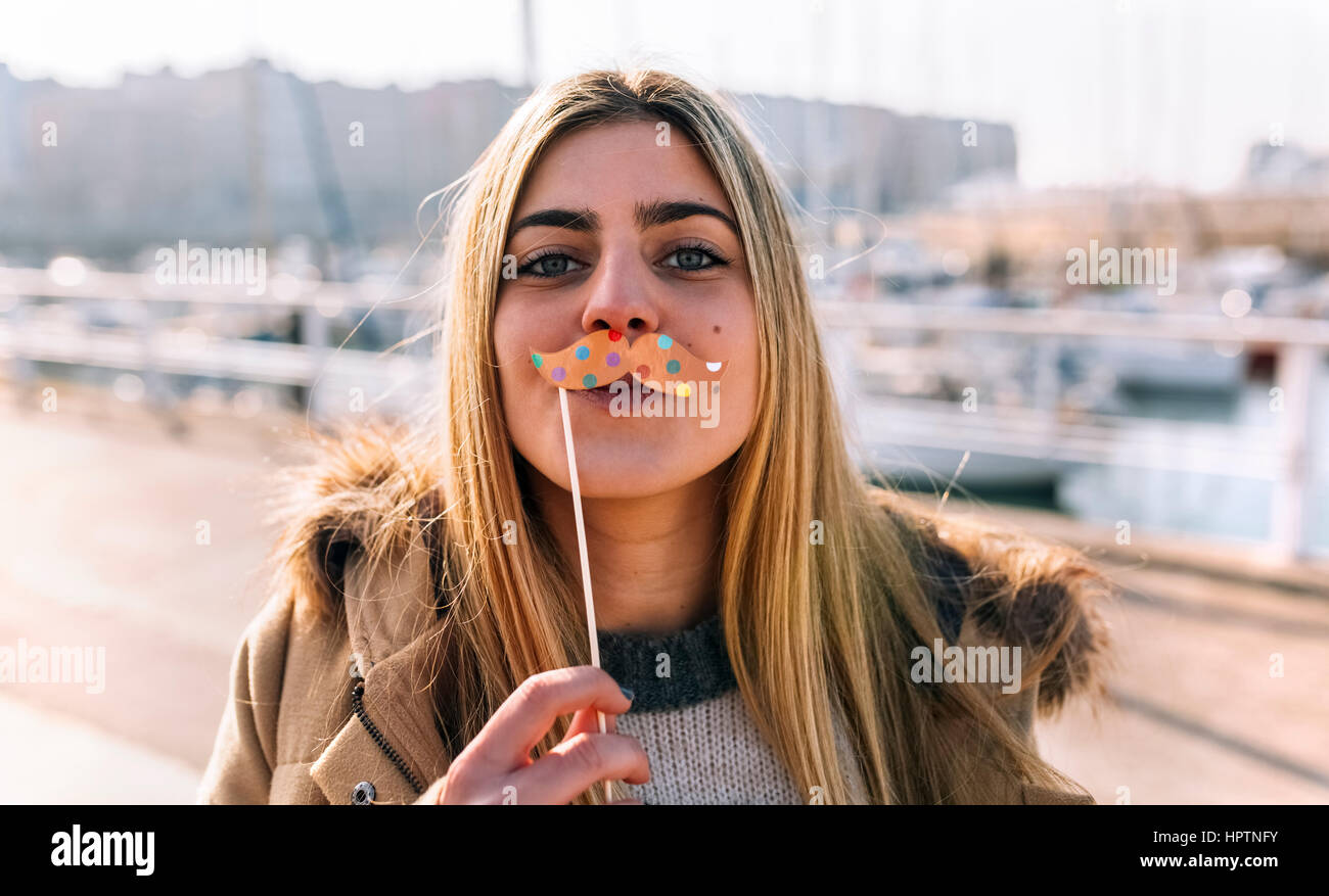Portrait of teenage girl with toy moustache - Stock Image