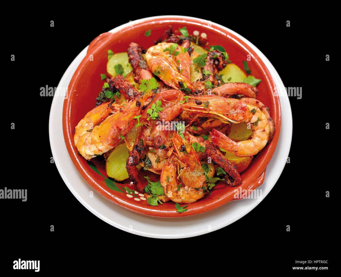 Close up of a octopus and shrimp dish in a teracotta plate with black background - Stock Image