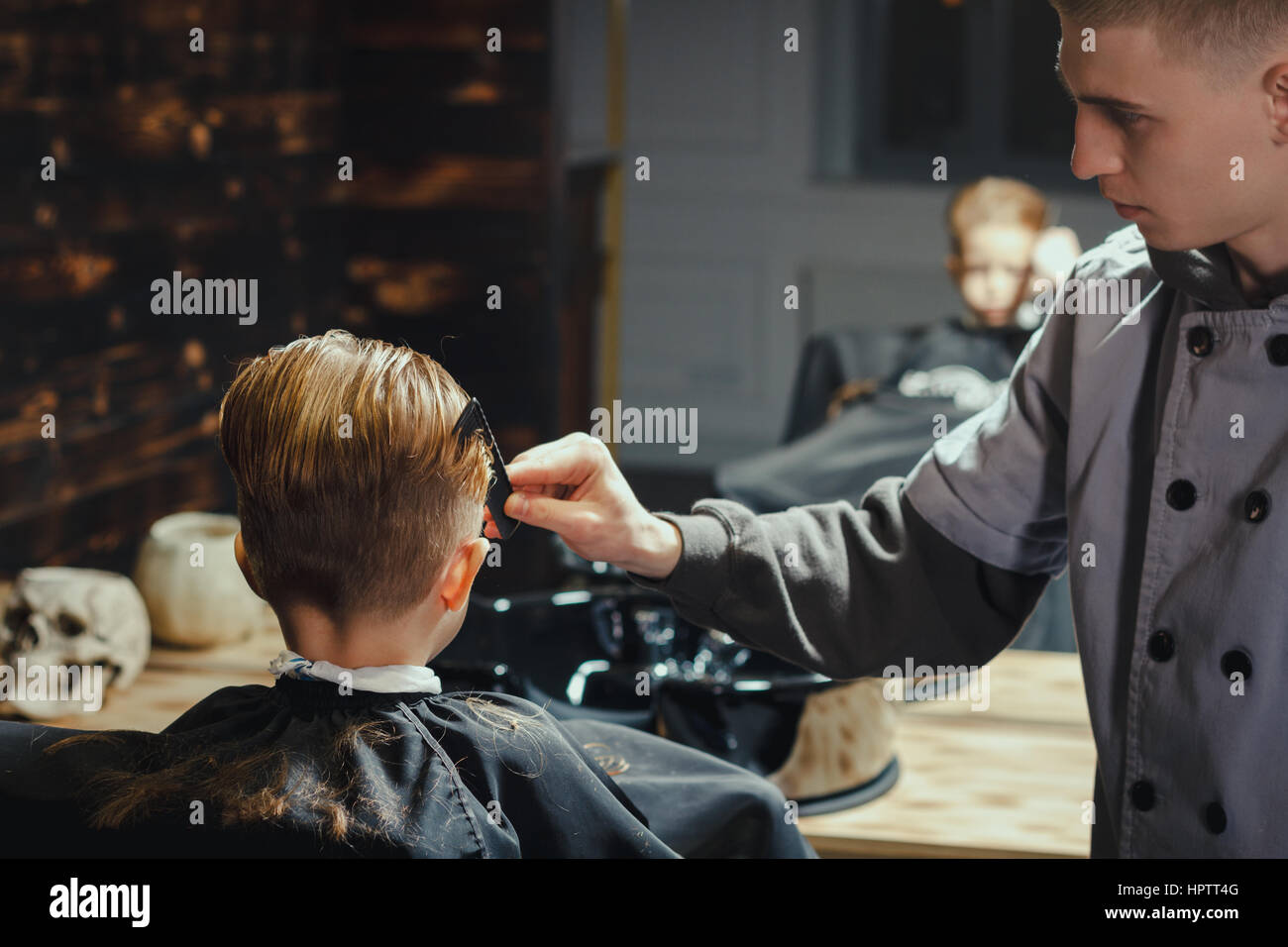 Little Boy Getting Haircut By Barber While Sitting In Chair At Stock