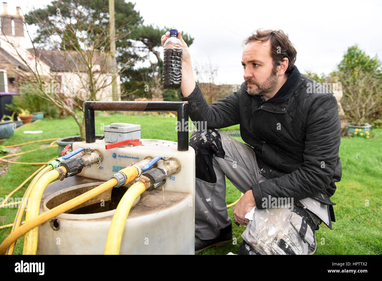 Heating engineer plumber power flushing a domestic central heating system - Stock Image