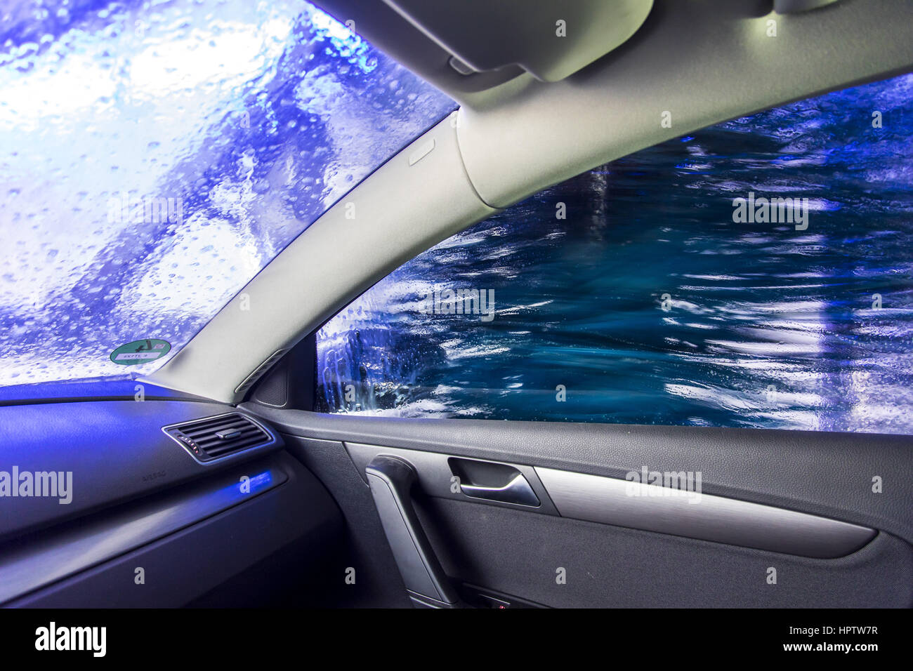 Car in an automatic car wash site, cleaning foam is sprayed on, rotating cleaning brush, - Stock Image