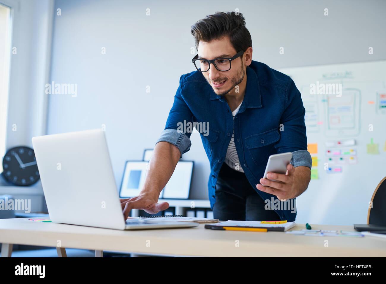 Programmer, web developer, designer working at office comparing mobile and desktop website versions - Stock Image