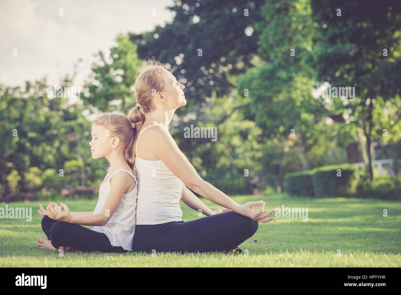 Mother and daughter doing yoga exercises on grass in the park at the day time - Stock Image