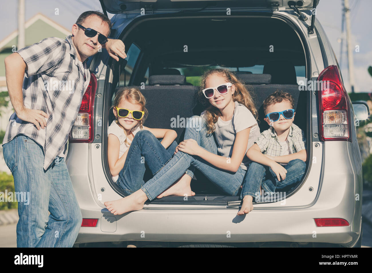 Happy family getting ready for road trip on a sunny day.  Concept of friendly family. - Stock Image