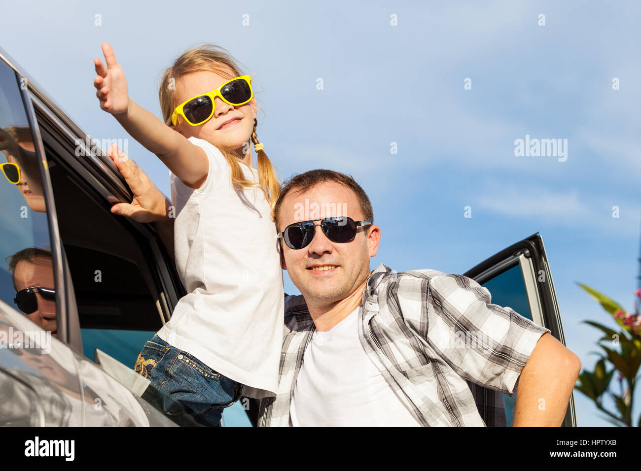 Happy father and daughter getting ready for road trip on a sunny day.  Concept of friendly family. - Stock Image