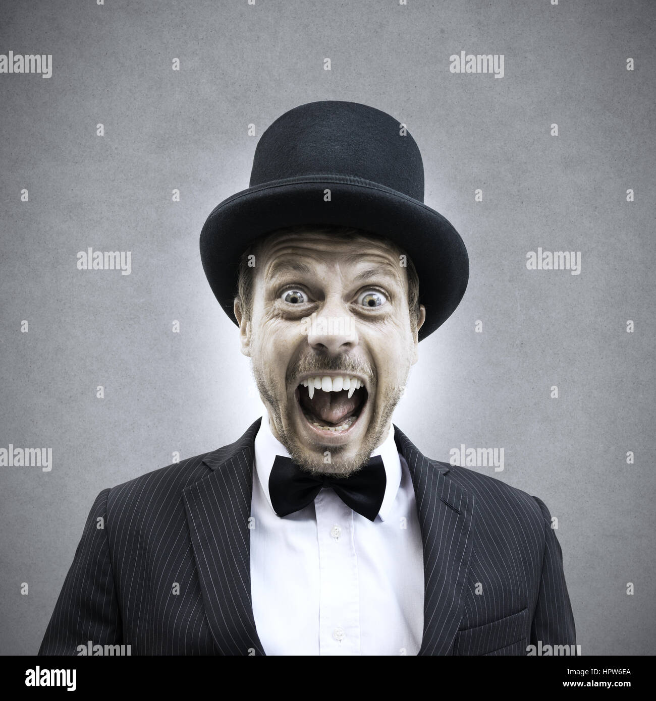 Scary vampire businessman screaming and showing fangs in vintage elegant outfit. Stock Photo