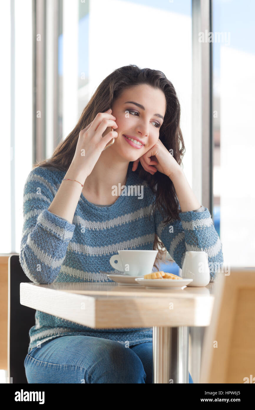Smiling girl sitting at bar table and having a call with her smart phone - Stock Image